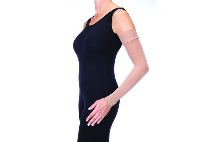 Woman in black dress wearing skin tone compression sleeve on arm