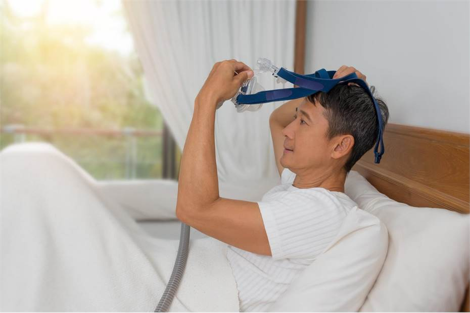 Man in bed putting his CPAP mask on