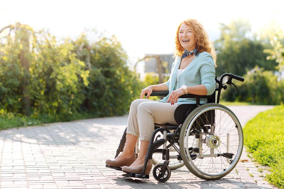 Woman laughing in a manual wheelchair outside