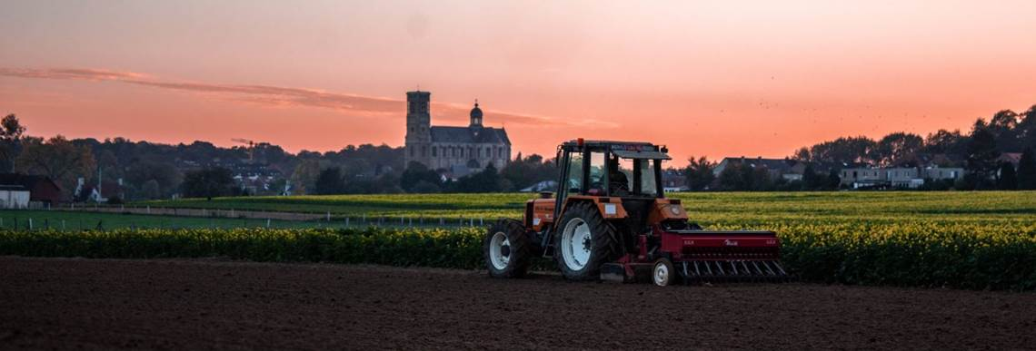 Tractor Mowing in Sunset