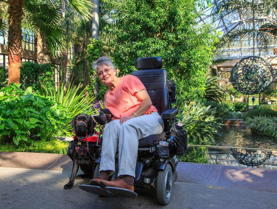 lady on a power wheelchair enjoying the outdoors with her dog