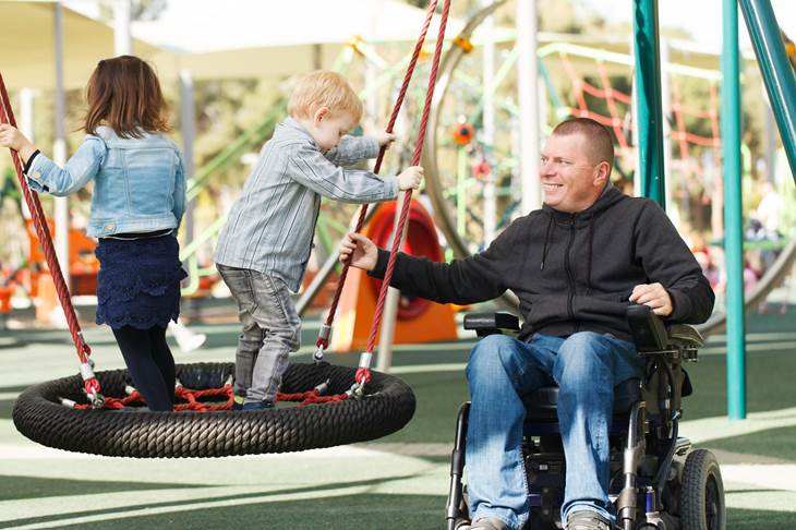 Father in wheelchair playing with children