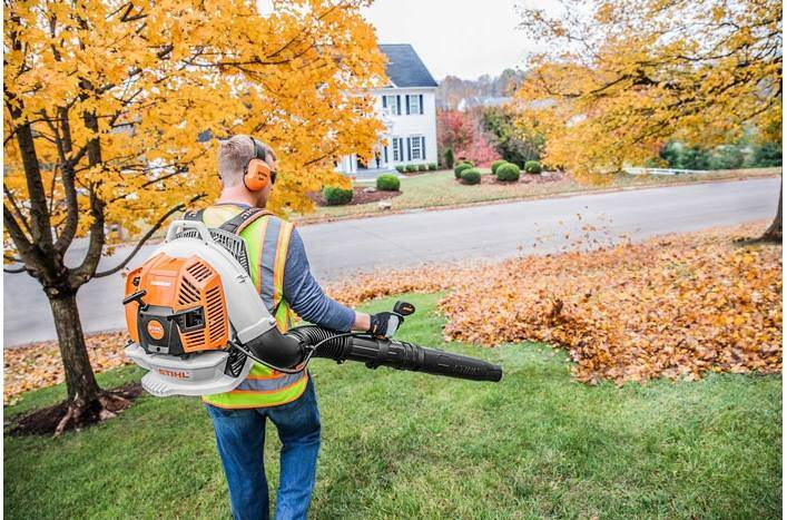 Man using STIHL leaf blower on a lawn next to trees