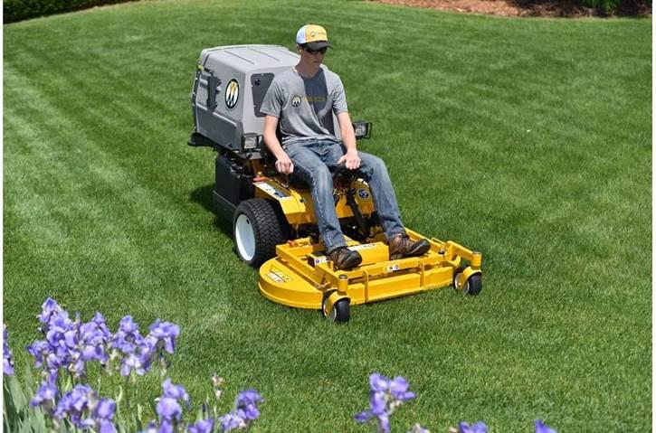 Young man using a zero-turn Walker mower on a freshly cut lawn behind a bush of flowers