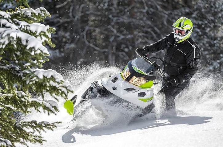 man on snowmobile carving up snow