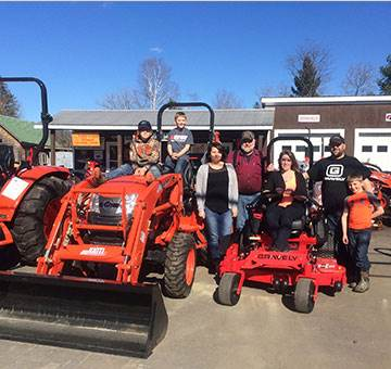 Jon Parks Tractor family sitting on Gravely Mowers & KIOTI tractors