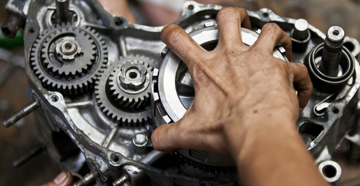 Mechanic working on motorcycle engine