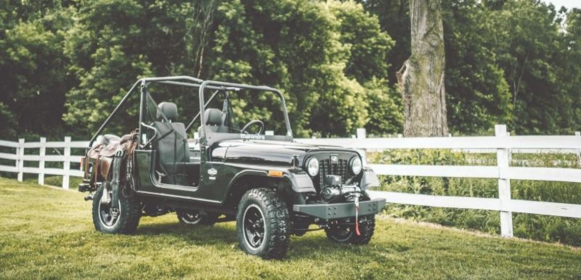 Mahindra Roxor off-road vehicle parked in the field near a fence