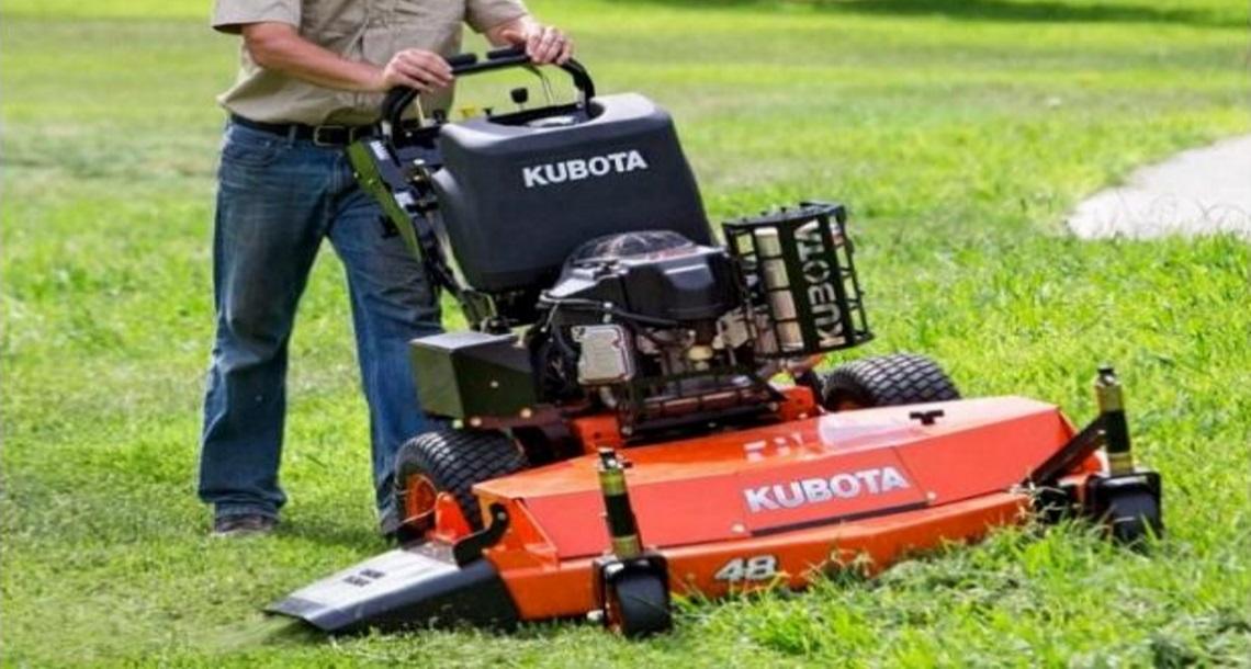 Man using an orange Kubota zero-turn mower