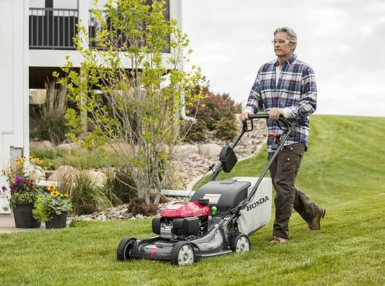 A man using a push mower on his lawn