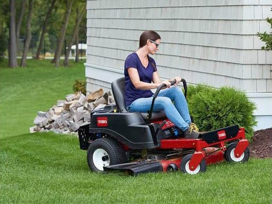A woman using her riding mower to mow her lawn