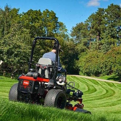 A man using a commercial Toro riding mower on a his lawn
