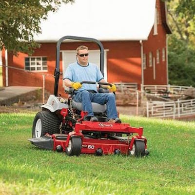 A man using a riding Exmark mower on his lawn