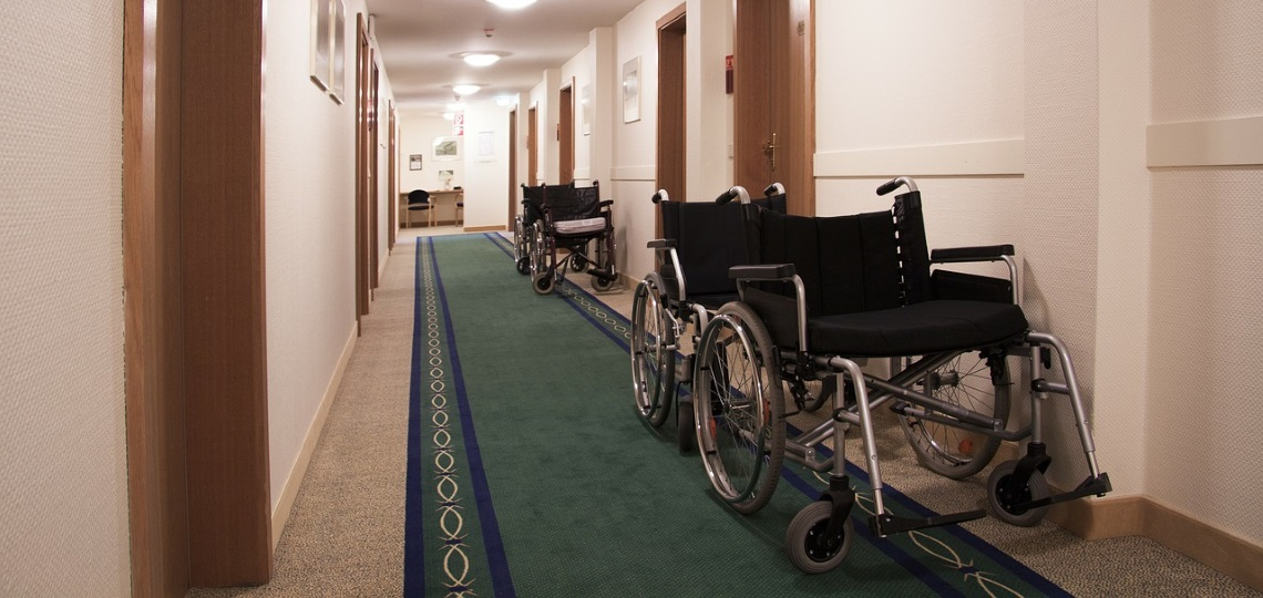 a row of manual wheelchairs in a hallway