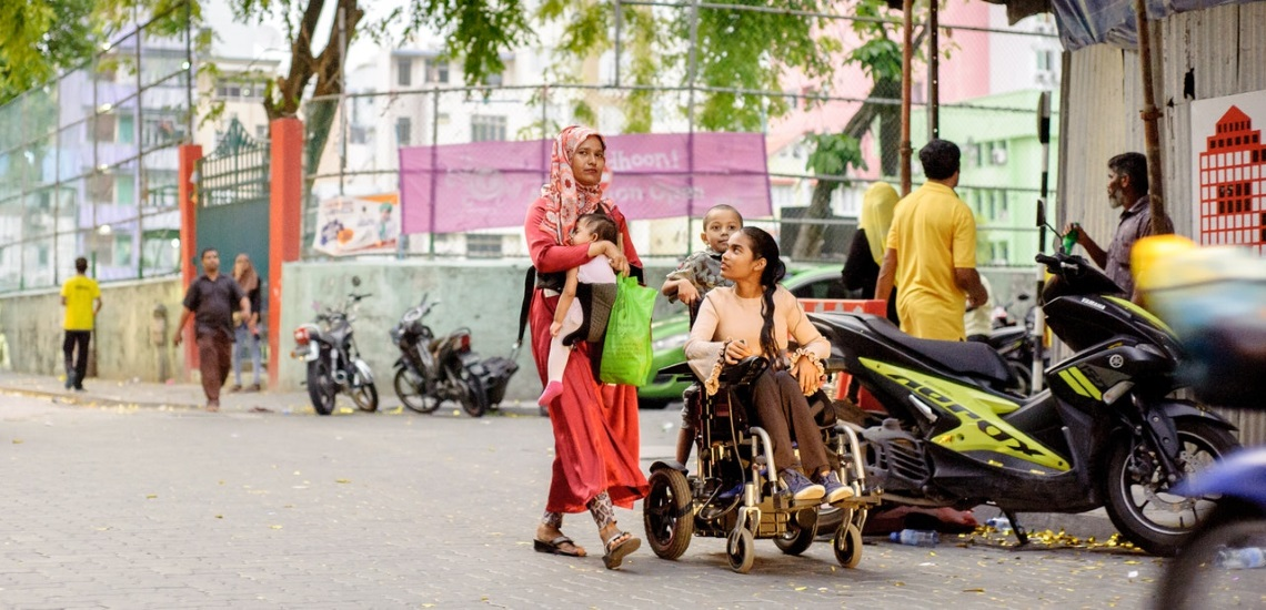 A Family walking on the street meanwhile a girl is using a power wheelchair
