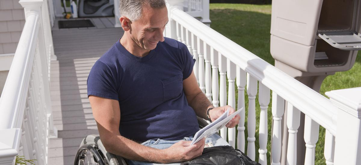 Man in Wheelchair looking at mail