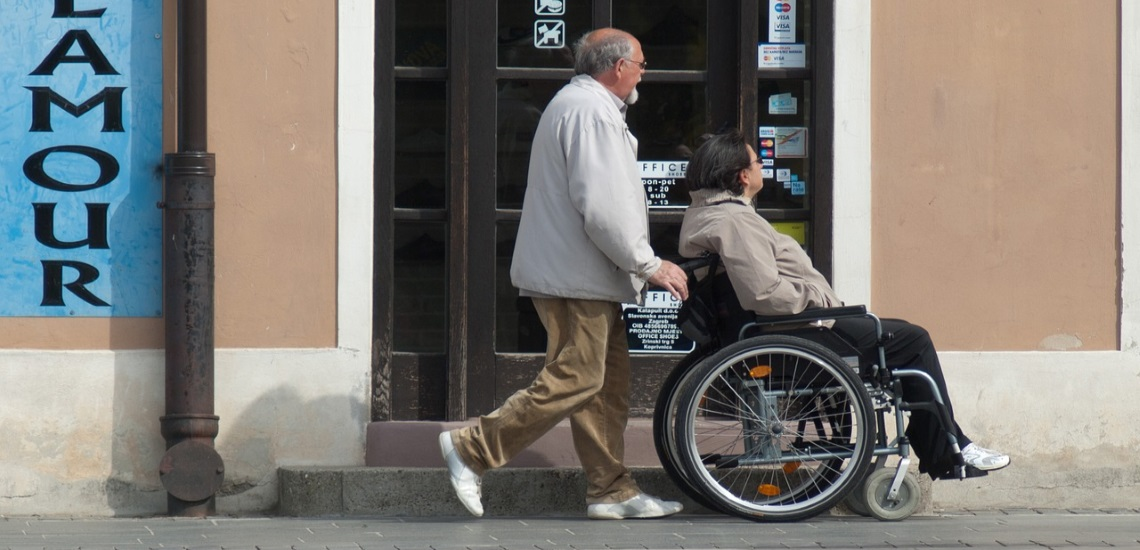 A old man pushes another person with black hair in a wheelchair past a storefront.