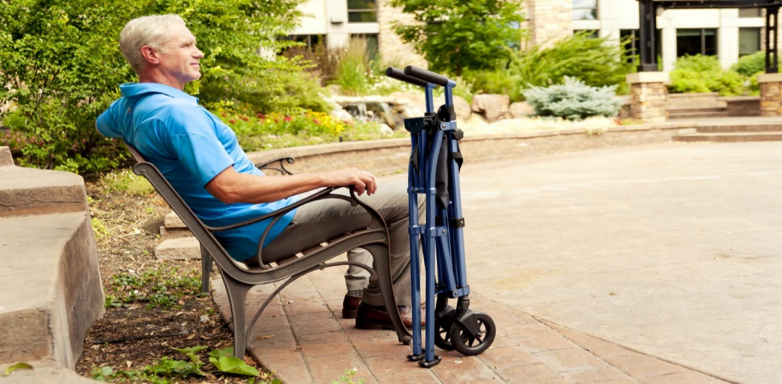 Man sits on bench outside with a folded up walker
