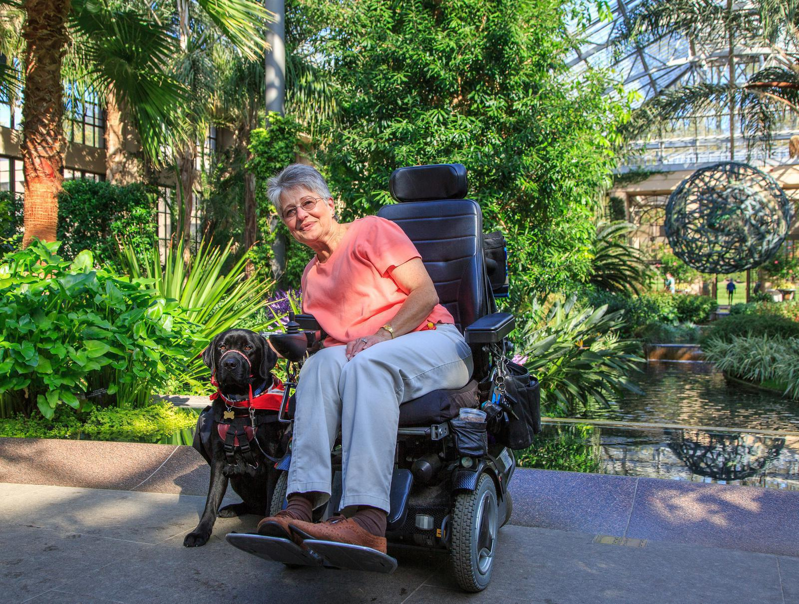 Woman posing with her service dog in her power wheelchair