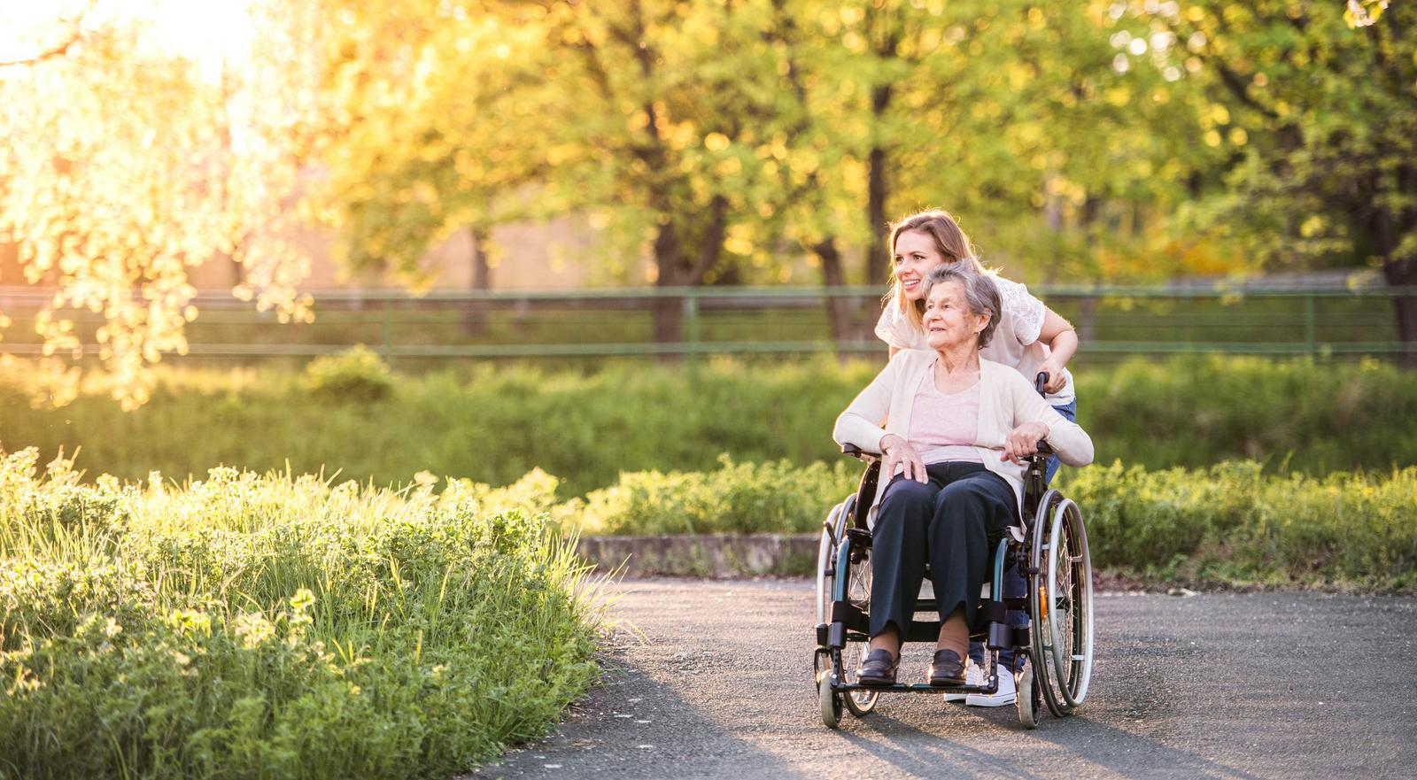 Woman pushing an elderly woman in a wheelchair