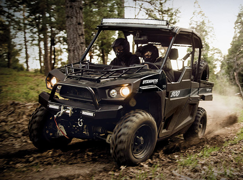 Two people speeding on a muddy trail in a black Textron Off-Road sport side by side.