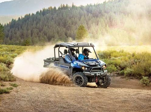 Two people drift on a dirt trail, kicking up dust in a Textron Off-Road utility side by side.