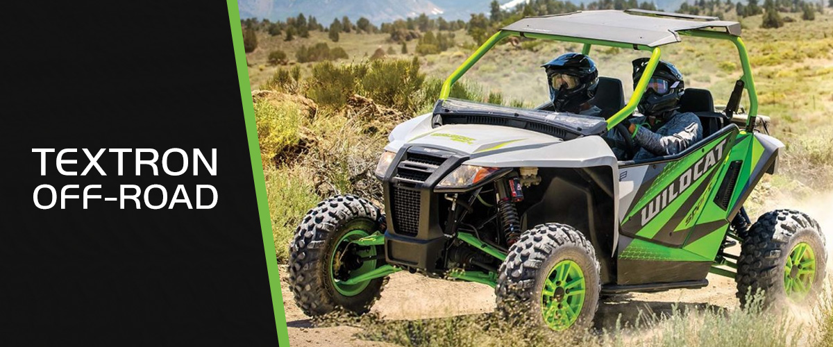 Two people riding in a Textron Off Road side by side on a dirt trail.
