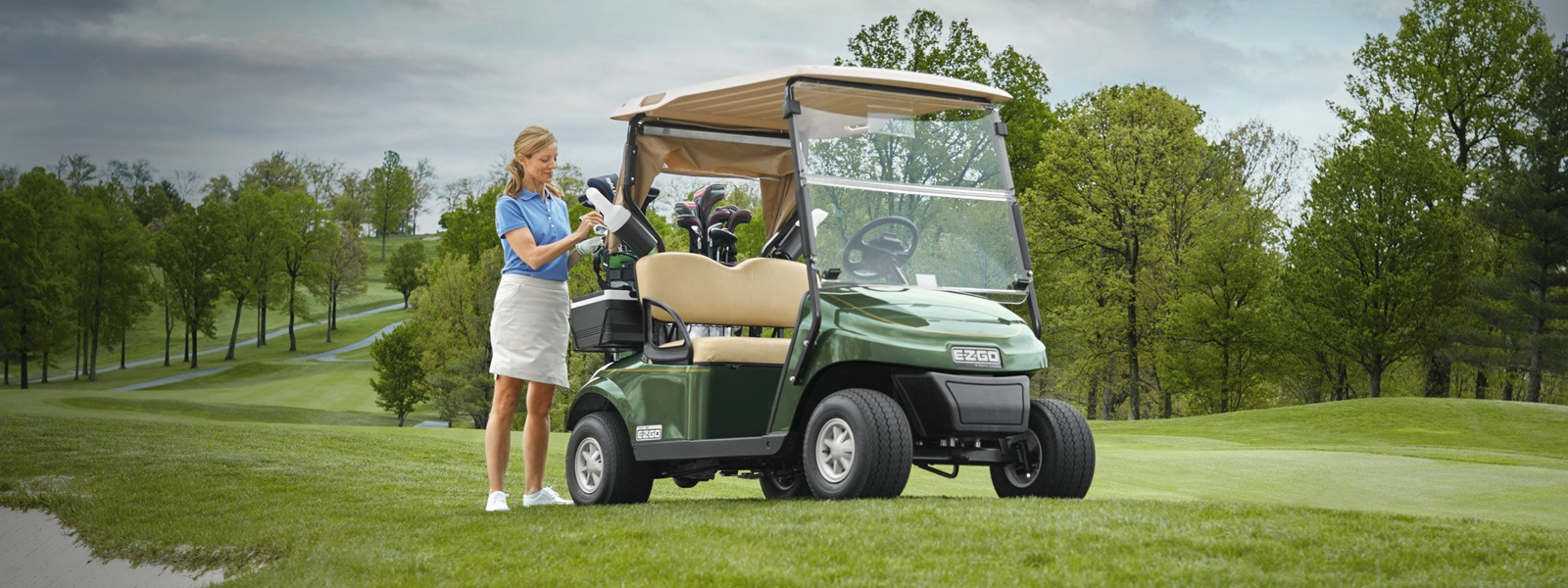 A woman next to a green E-Z-GO golf cart take a golf club out of the back.