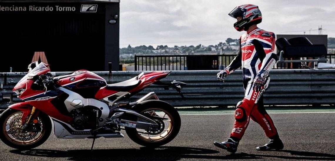 a man walking to his custom 2019 Honda® CBR1000RR motorcycle