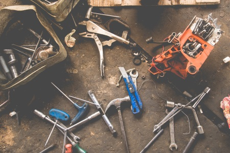 Various tools layed out on the floor of a concrete garage floor