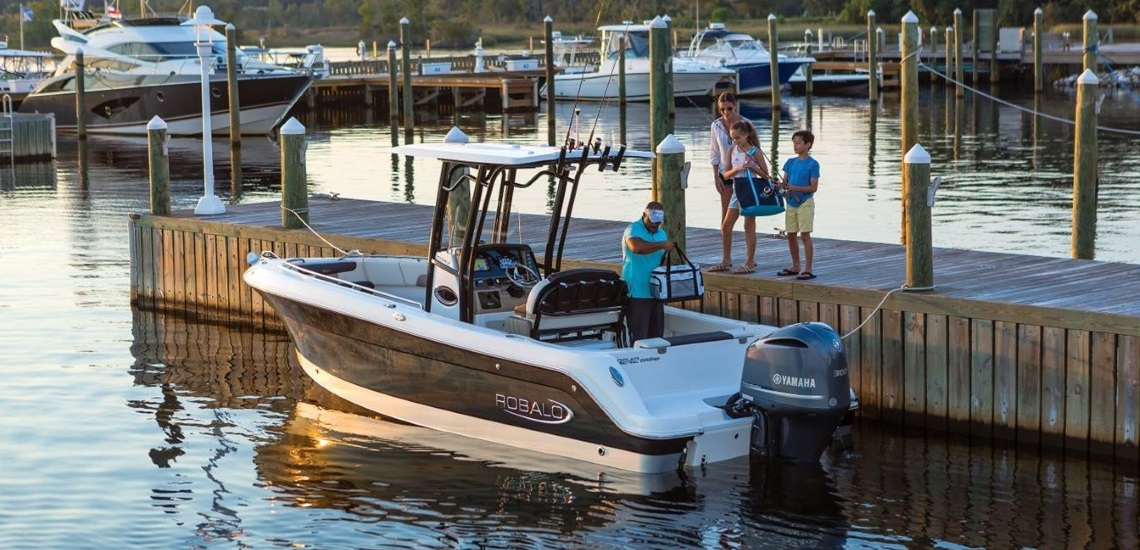 A family preparing to board a 2019 Robalo 242 Explorer boat in a marina