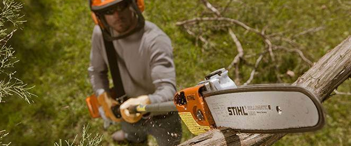 A man uses a STIHL® chainsaw with an extended handle to cut a high branch.