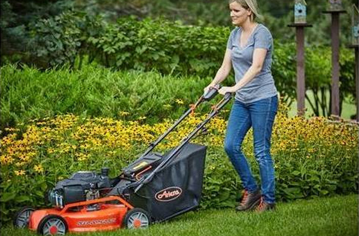 A woman pushes an Ariens walk behind mower alongside a flowerbed.