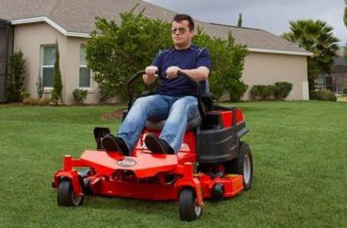 A man wearing sunglasses rides an Ariens zero-turn mower in his front yard.