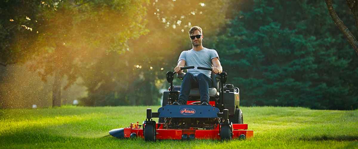 A man wearing sunglasses rides an Ariens zero-turn mower on a large lawn at sunset.