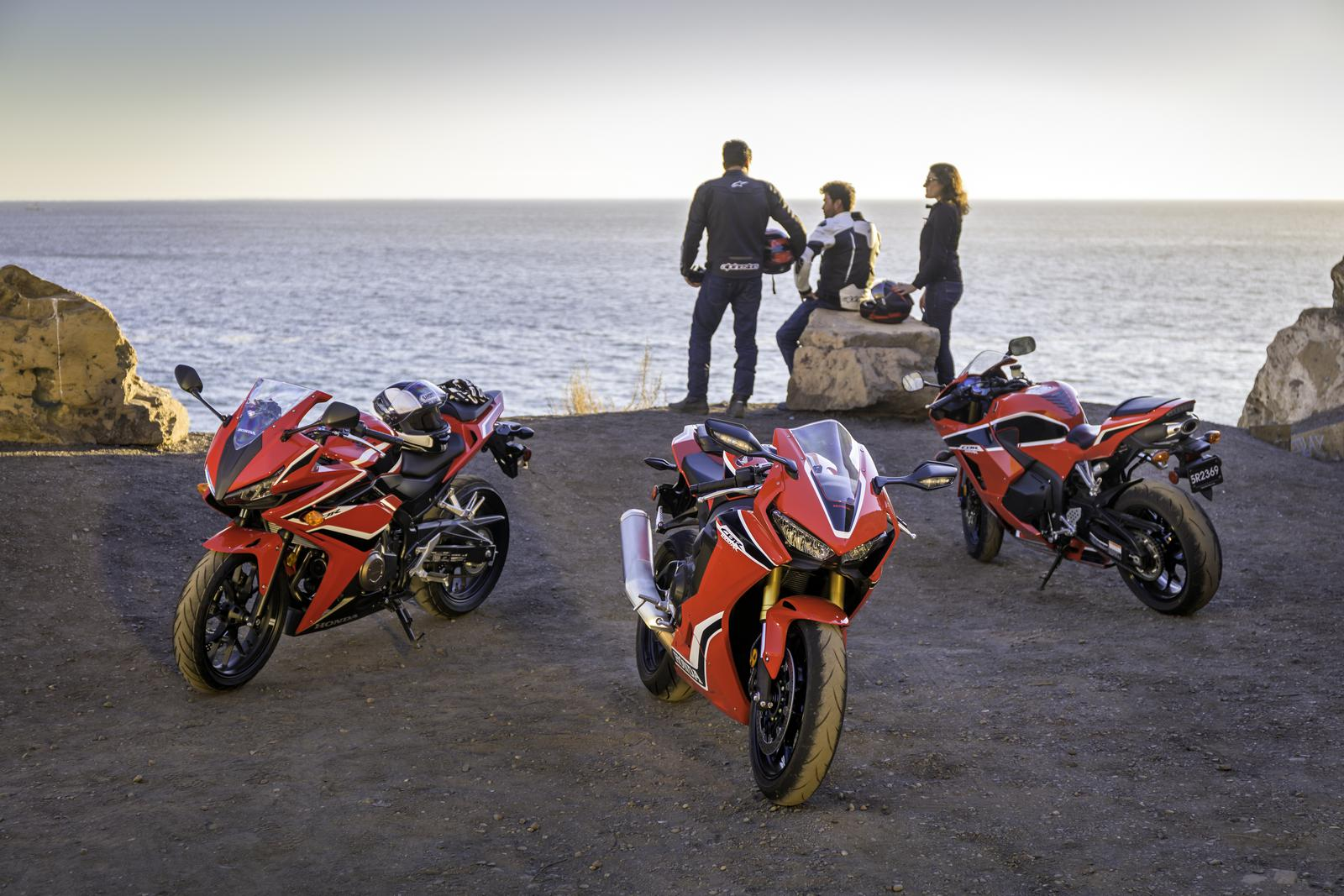 Friends enjoying a view with red Honda Street Bikes