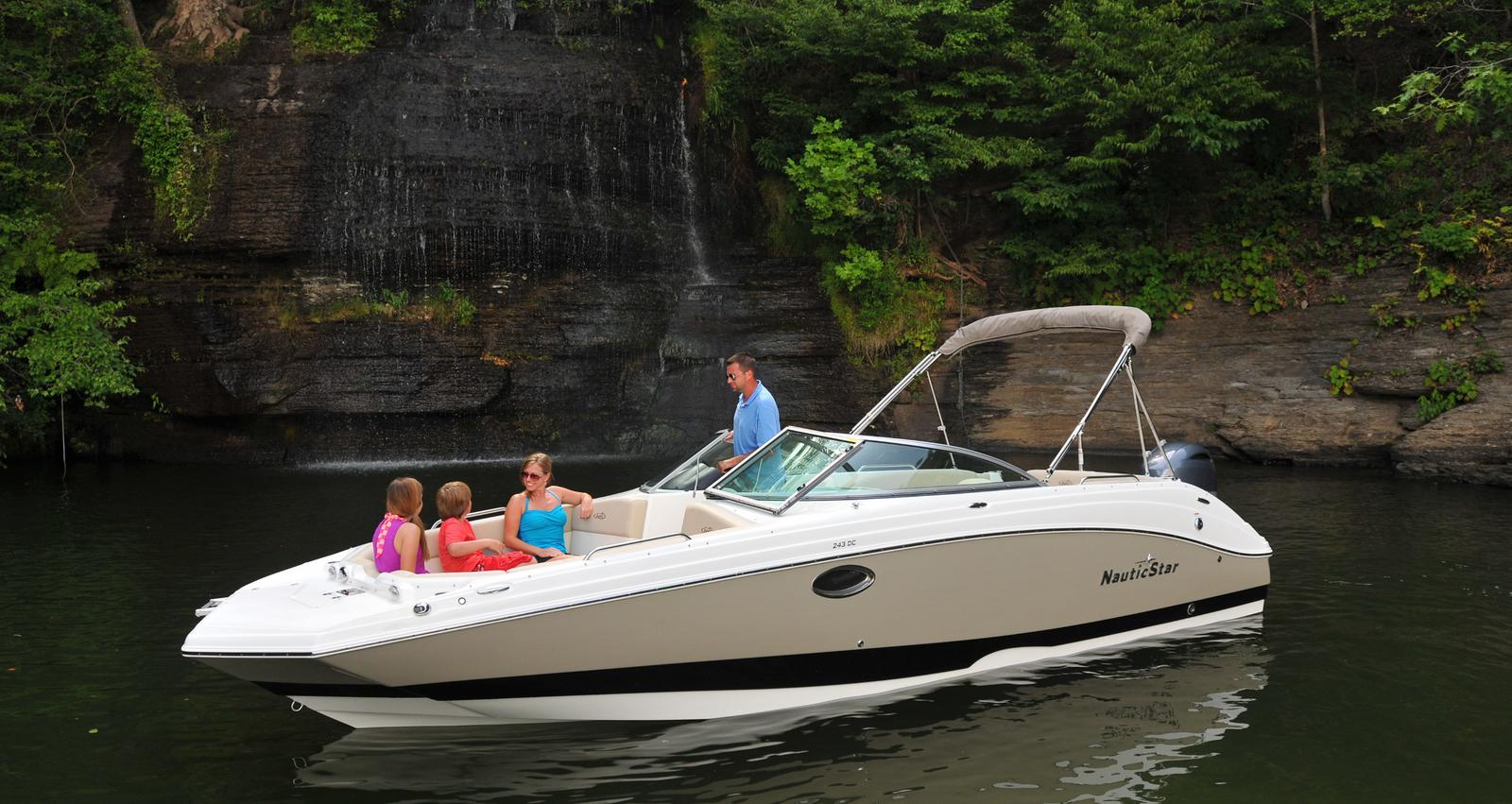 Family riding in their NauticStar deck boat near a waterfall