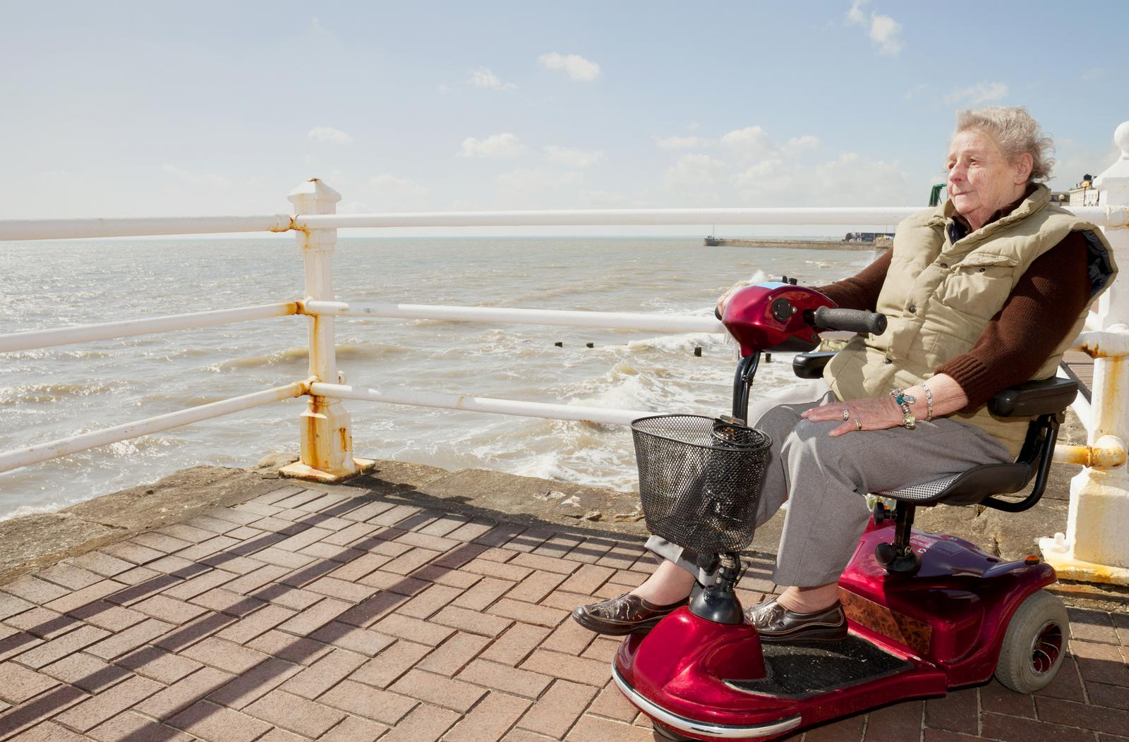 Woman using her mobility scooter on a dock near the ocean