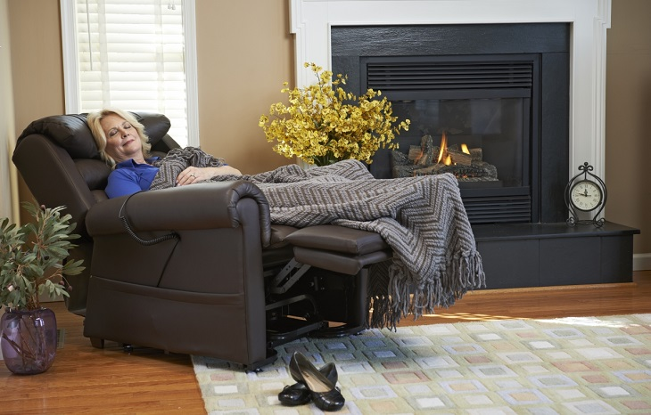 woman sleeping in lift chair next to fire