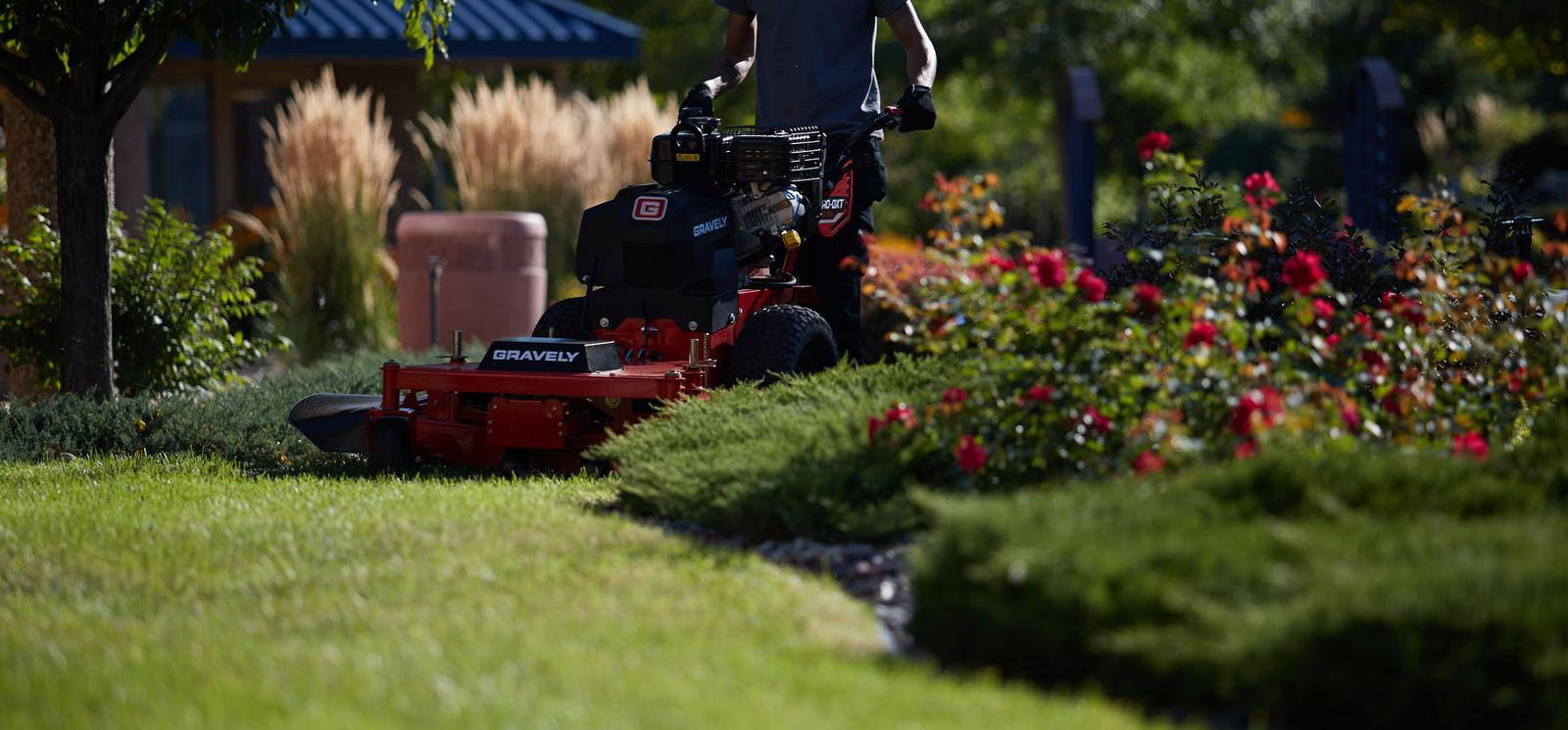 Man using a standing Gravely lawn tractor in yard