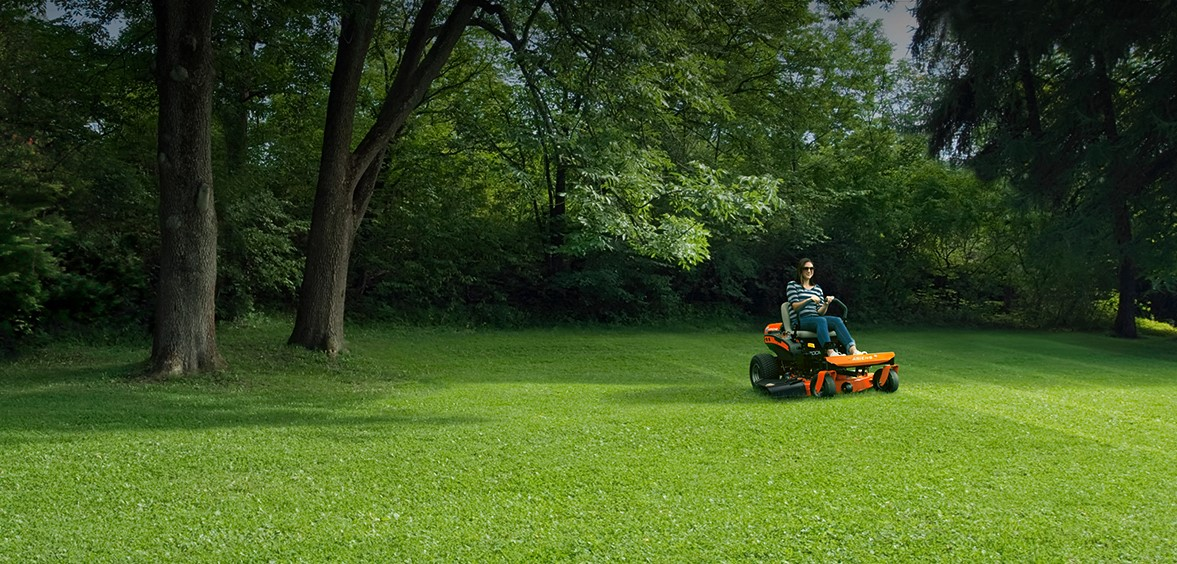 Man using lawn tractor on large patch of grass