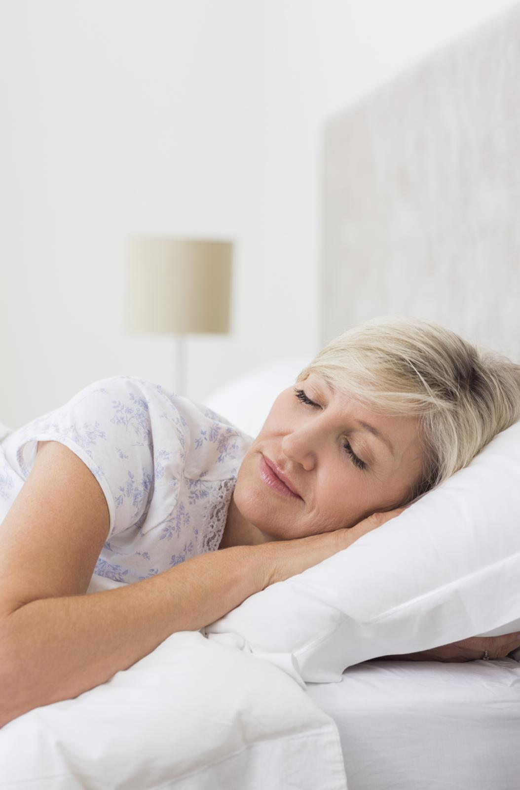 Mature-woman-sleeping-with-eyes-closed-in-bed-000058707446_Medium