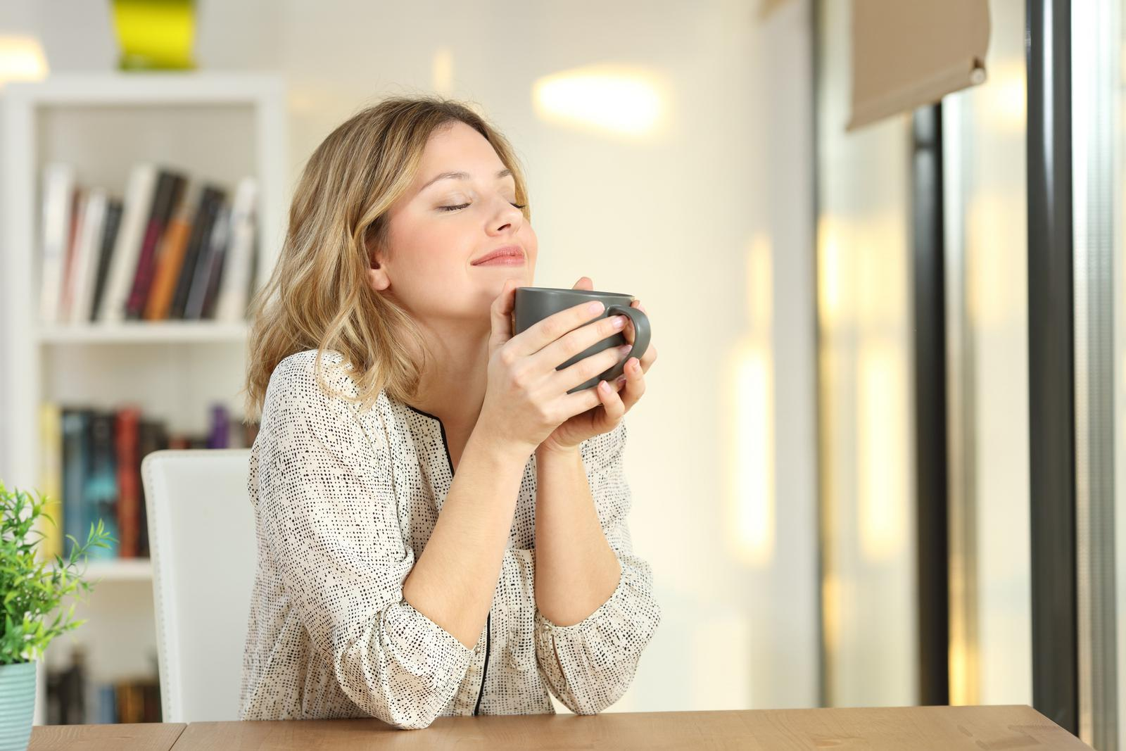 Woman with clear skin drinking coffee