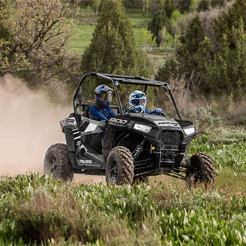 A couple driving a 2019 Polaris Industries RZR® S 900 EPS at full speed