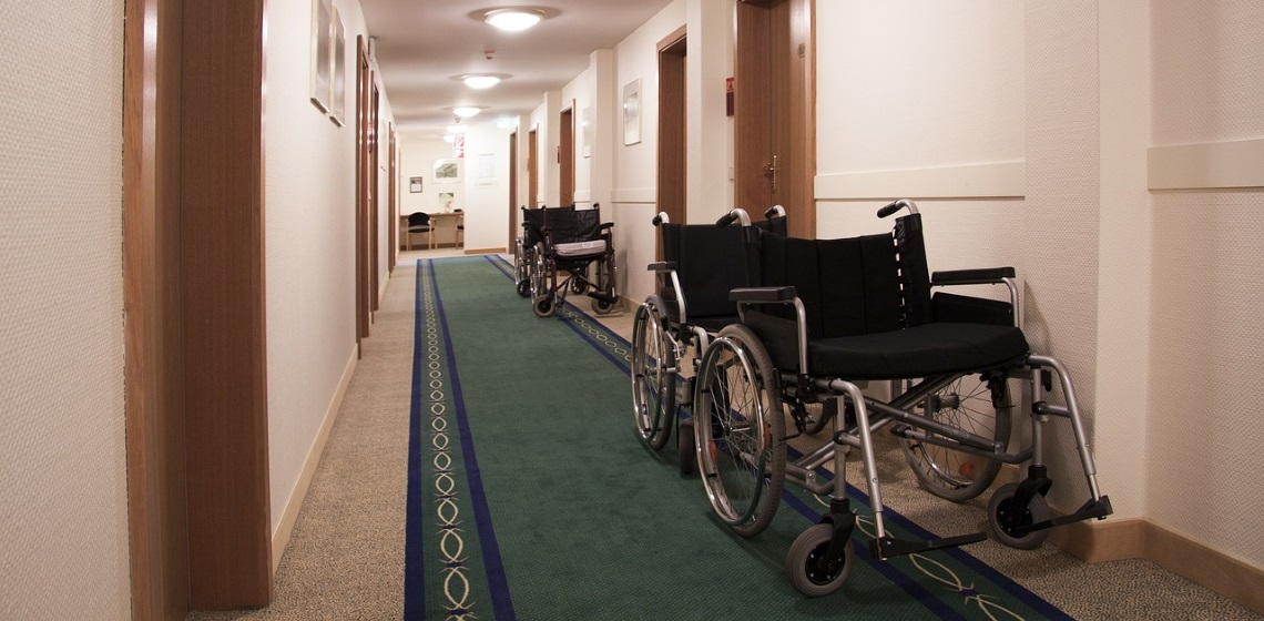 a group of wheelchairs lined up in a corridor ready to be used