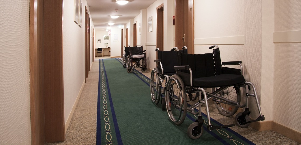 A pair of manual wheelchairs in a corridor