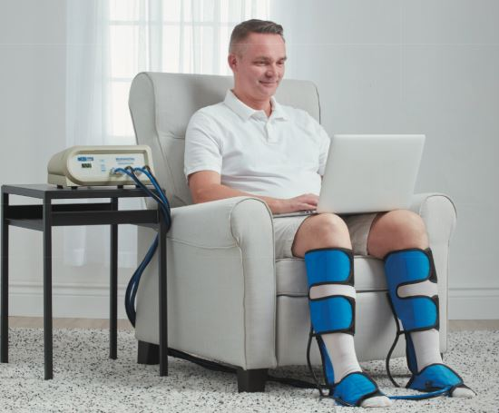Man sitting in chair doign this compression therapy with a IC-BAP-DL on his calves and ankles connected to compression pump