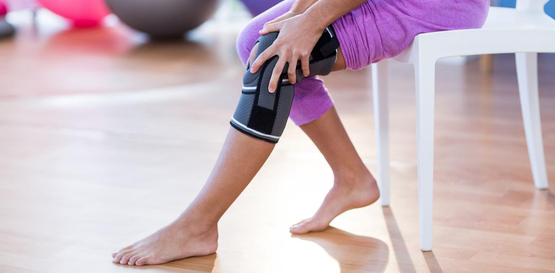 Woman adjusting her orthopedic knee brace