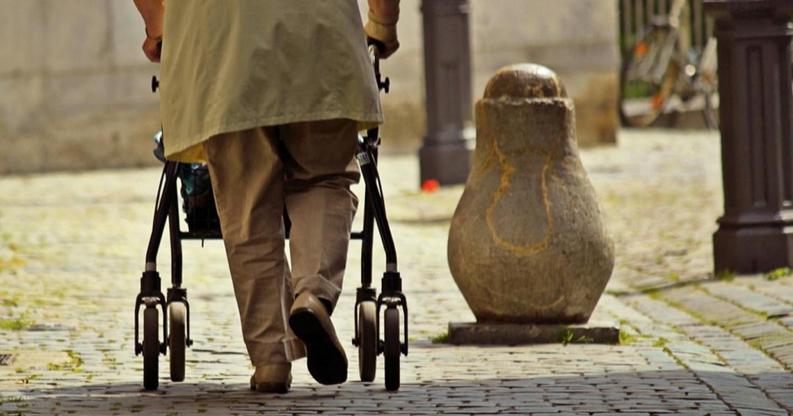 man walking on cobblestones with his walker rollator