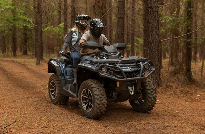 Couple riding Can-Am Utility ATV through woods  in Durham, NC